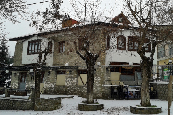 A building that follows the traditional local architecture at the snowy square of Samarina.