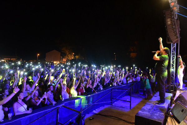 A photo showing members of a band on the stage and crowd at the audience during the Ireon Music Festival of Samos.