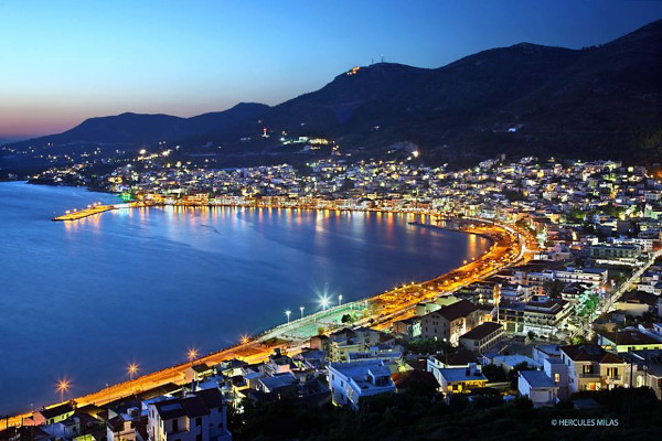 A panoramic picture of the Samos town and its port with its lit promenade.