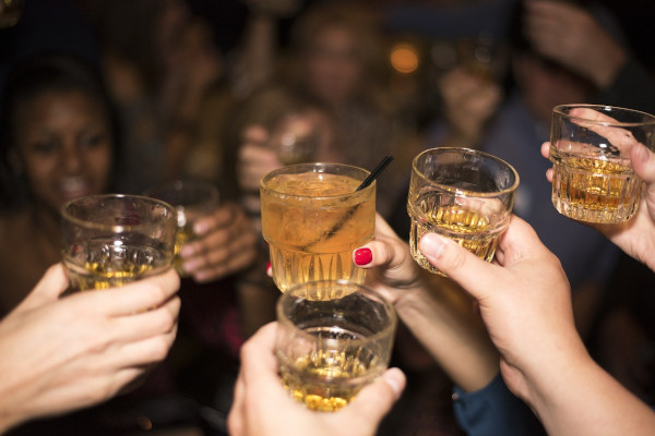 A close up of hands holding glasses with alcohol making a toast.