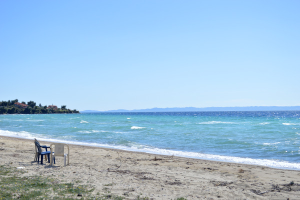 A photo showing some plastic chairs and a part of the beach of Nikiti of Halkidiki.