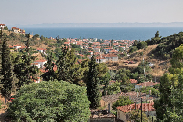 An overview of the village of Nikiti where trees grow among houses and the blue sea is in the background.