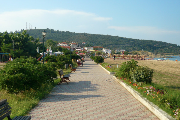 The paved coastal promenade which is exactly by the sandy beach.