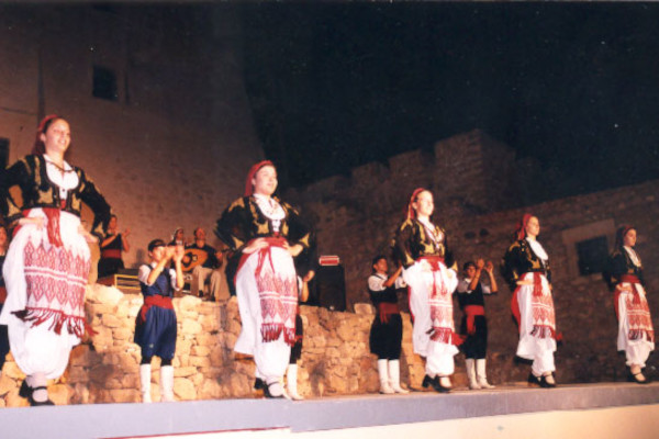 A band and dancers with traditional clothes are dancing during a performance of Kornaria Summer Festival of Sitia.