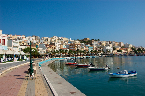 The pedestrian coastal route of Sitia on Crete with white buildings on the left and blue sea on the right.
