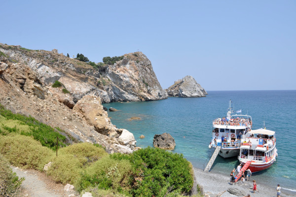 Two boats, full of tourists, anchored by a beach during a daily cruize trip.