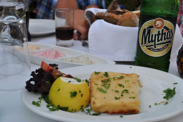 The famous saganaki as an appetizer and a Greek beer called Mythos on a table of a restaurant.