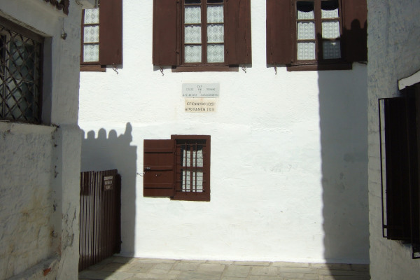 The front part of the House - Museum of Papadiamandis with a wall sign informing about the place.