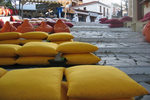 The outdoor seating area of the famous pillows bar with many pillows on the cobblestone steps.