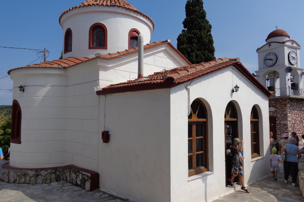 A picture of the church's exterior including the main entrance of St. Nikolaos Church of Skiathos and its Clock Tower.