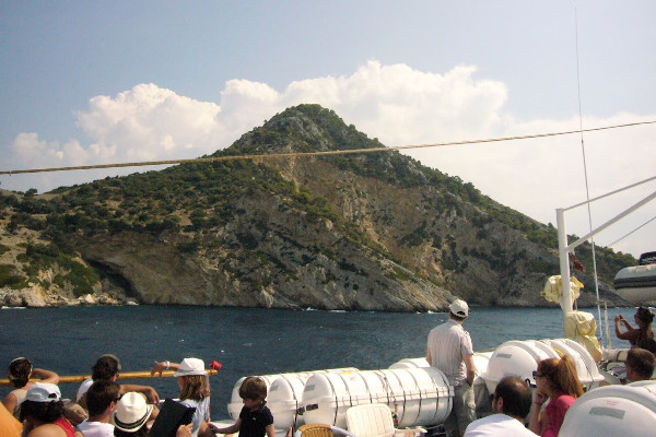 People on the deck of the cruise ship admire the landscape composed by the sea and the nearby coast.