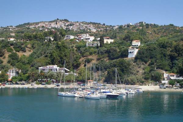 A photo that depicts sailing boats anchored at the port of Loutraki, and the village of Glossa at the top of the hill.