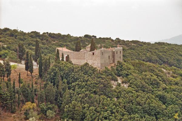 An overview of the Agia Varvara Monastery of Skopelos among dense vegetation.