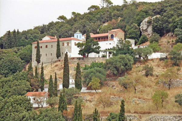 A distant photo of the Timios Prodromos Monastery in Skopelos among the dense vegetation of the slope it is located.