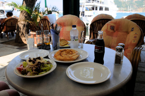 An image with a Greek salad and a Skopelos Cheese Pie on a table at a restaurant in front of the port.
