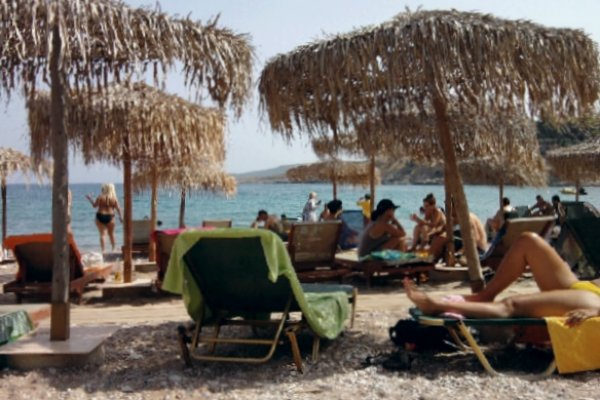 People on sun beds and umbrellas at the Agia Marina (Paradise) Beach of Spetses.