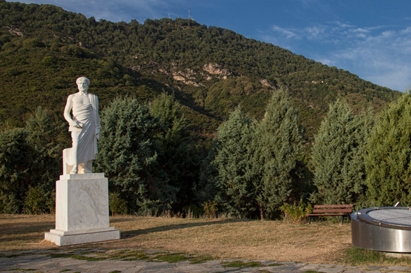 The statue of Aristotle, an interactive instrument, and the mountain behind the Aristotle's Park.