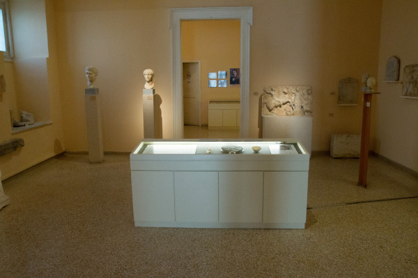 One of the rooms of the Archaeological Museum of Syros in Ermoupolis with exhibits close to the walls and a display.