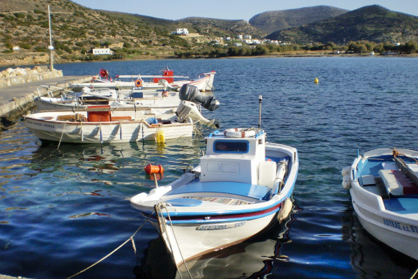 Some small fishing boats anchored in the port of Galissas and hills in the background.
