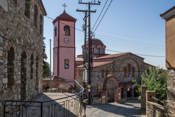 The stone-built main church and other buildings by a street of Taxiarchis village of Halkidiki.