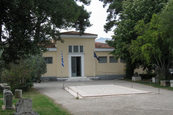 The building and the main entrance of the Archaeological Museum of Thasos between tall green trees.