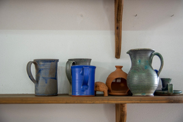 A bench with items displayed in the Folklore Museum of Limenaria such as metal jug and glasses.