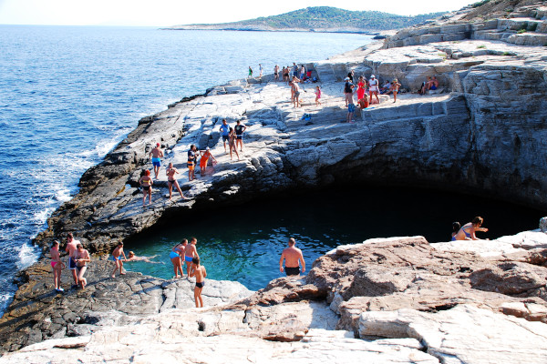 People swim in the waters of the lagoon and others sunbathe around the lagoon of Giola.