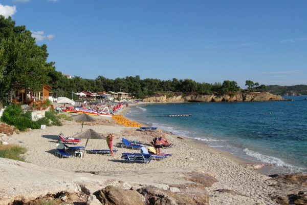 A photo showing people sunbeds and umbrellas at Pefkari Beach on Thasos island.