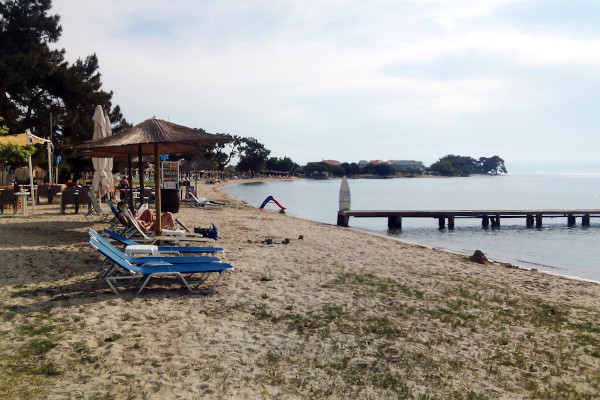 A photo showing sunbeds, umbrellas, and a wooden pier of the beach of Skala Rachoniou on the island of Thasos.