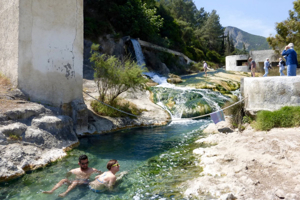 Two people enjoying their bath in the stream of the Hot Springs of Thermopylae during a sunny day.