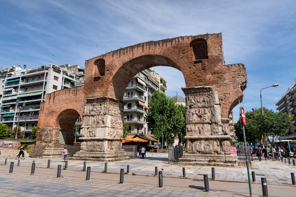 The Arch of Galerius with some big buildings and the blue sky as a background.