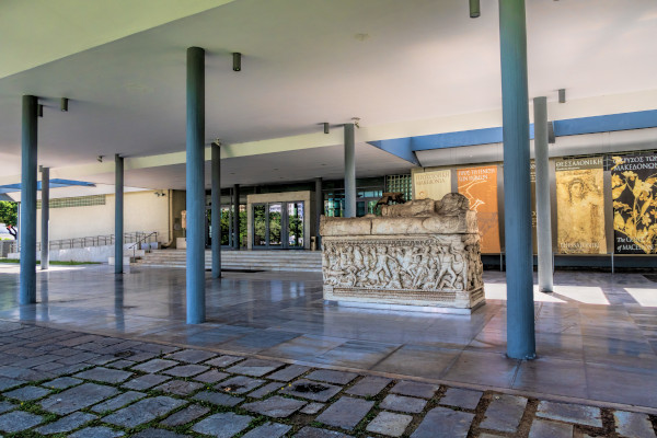 The main entrance of the Archaeological Museum of Thessaloniki and an exhibit of a sarcophagus (stone coffin).