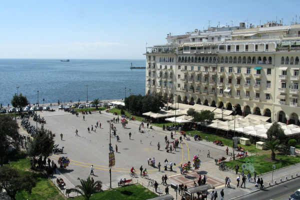 A panoramic picture showing people in Aristotelous Square with a building and the sea view as a background.