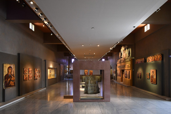 A room of the Byzantine Culture Museum of Thessaloniki with artifacts in displays and icons hanging on the walls.