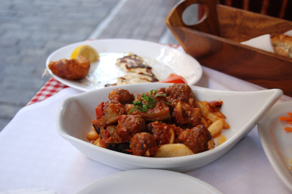 A dish of meat on a taverna table among other food dishes.