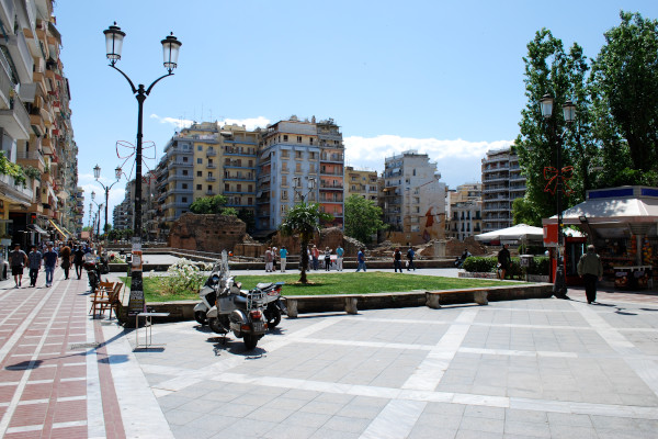 A picture of Navarinou Square and the ruins of Galerius Palace surrounded by high buildings.
