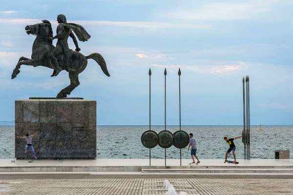 The statue of Alexander the Great with some skaters in front of it and the sea in the background.