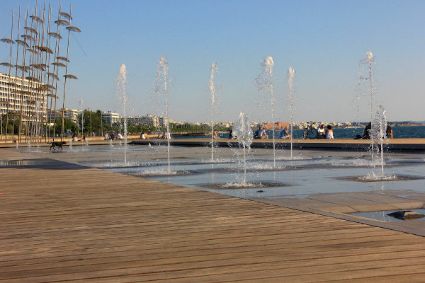 Water fountains, people relaxing or walking under the blue sky at the promenade of Thessaloniki.