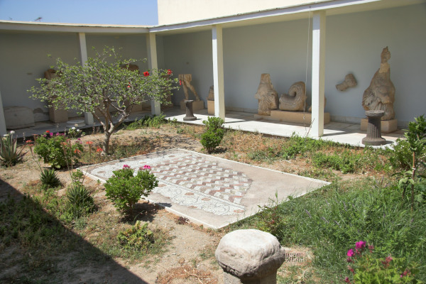 The inner yard of the Archaeological Museum of Tinos with sculptures around the walls.