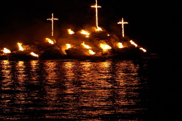 Three wooden crosses lit on fire, on the  rocky island opposite to Spitalia beach.