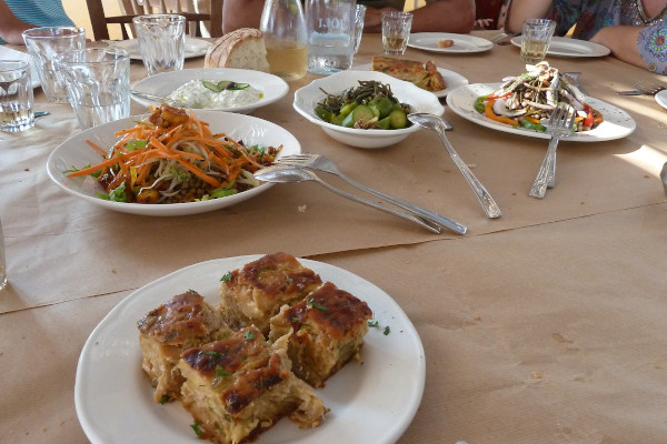 Salads and local dishes and bread on a table in a taverna of Tinos.