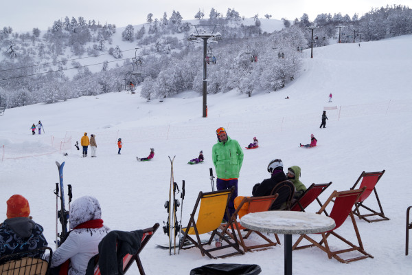 People in winter clothes sit on chairs by their ski equipment having the slope of Vasilitsa in the background.