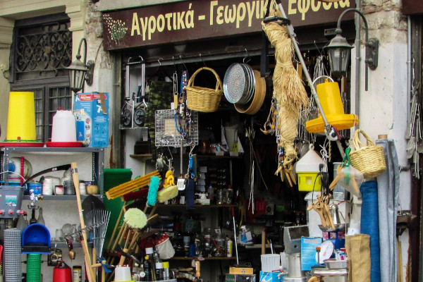 A traditional shop with many commodities on shelves and other hanging on the walls.
