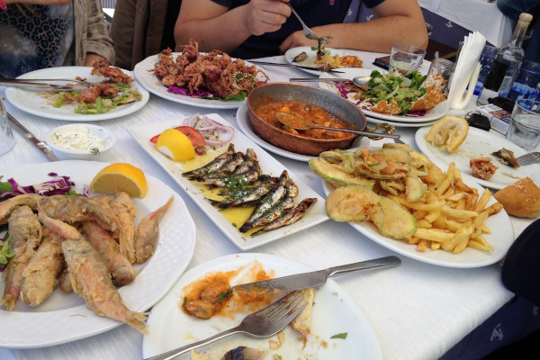 A taverna table full of different dishes to taste while the company drinks tsipouro the Greek distilled spirit.