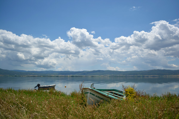 The waters of the lake reflecting the blue skies, one fishing boat lying at the shore and another is in the lake.