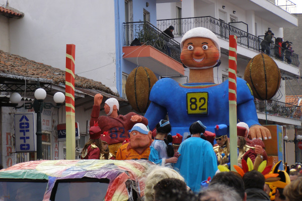 A carnival float surrounded by party observers passes through the roads of Xanthi.
