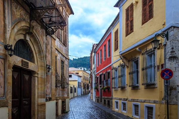 A narrow stone street between colorful buildings with traditional architecture in the old town of Xanthi.
