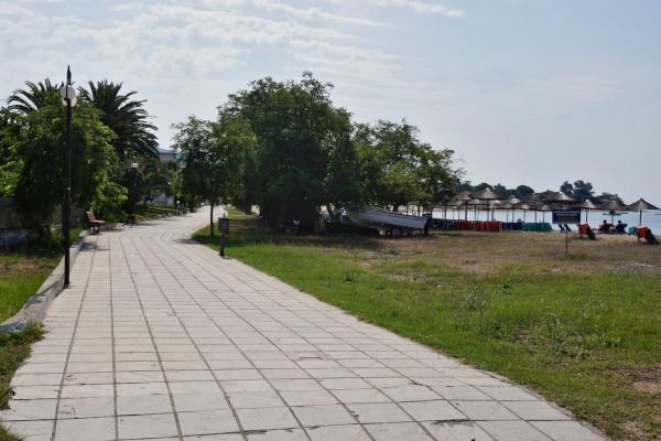 A paved path at the Yerakini coastline promenade that passes very close to the sandy beach.