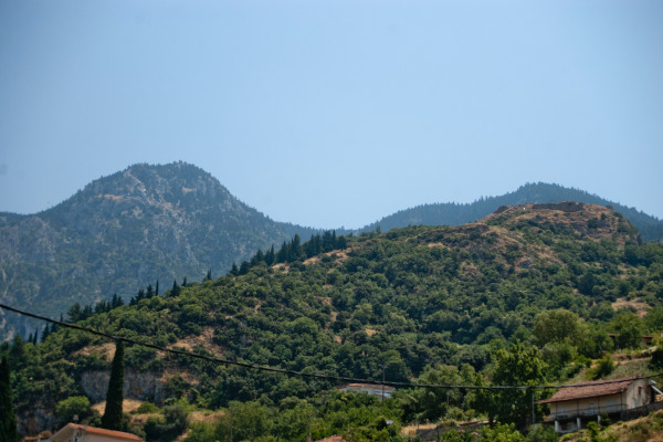 The hill of the Acropolis of Ypati covered by dense vegetation during a cloud-free day.