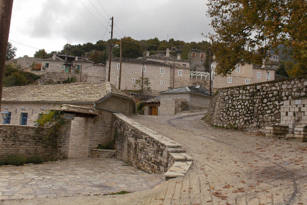 A cobble-stoned road and stone-built structures in a central part of Ano Pedina village at the Zagori area.